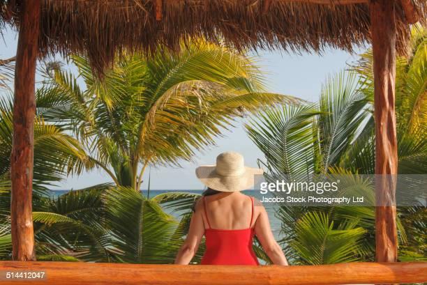 Hispanic woman sitting in hut on beach