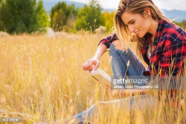 Hispanic woman sitting in tall grass reading book