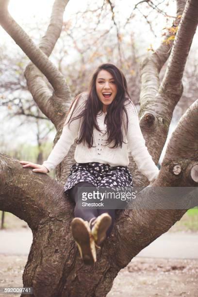 Hispanic woman sitting in tree