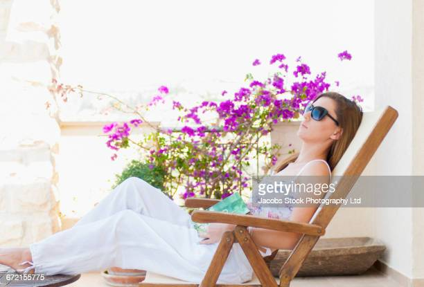 hispanic woman sitting on balcony holding book - republic of cyprus stock pictures, royalty-free photos & images