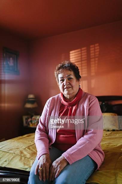 hispanic woman sitting on bed - 65 69 anos - fotografias e filmes do acervo