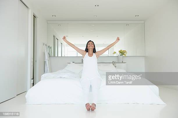 Hispanic woman sitting on bed with arms outstretched