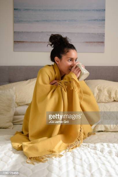 hispanic woman sitting on bed wrapped in blanket drinking coffee - hot tea stock pictures, royalty-free photos & images