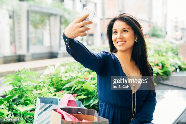 Hispanic woman sitting on bench posing for cell phone selfie