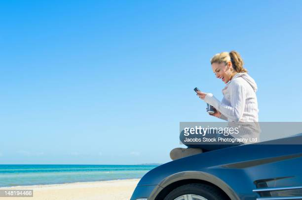 Hispanic woman sitting on car at beach using cell phone