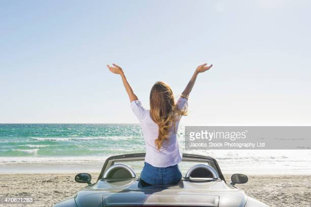 Hispanic woman sitting on convertible at beach