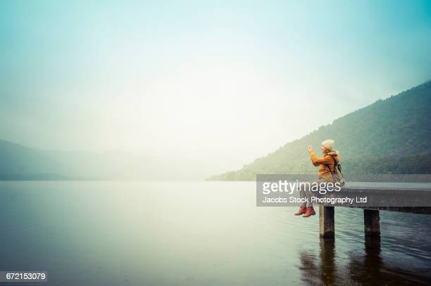 Hispanic woman sitting on dock at lake photographing mountain