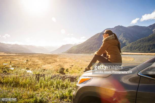 hispanic woman sitting on hood of car admiring scenic view - admiration stock pictures, royalty-free photos & images