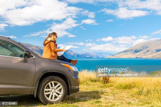 Hispanic woman sitting on hood of car at mountain lake reading map