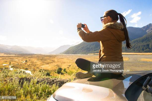 Hispanic woman sitting on hood of car photographing scenic view