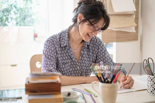 Hispanic woman sketching in home office