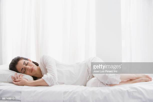 Hispanic woman sleeping in bed