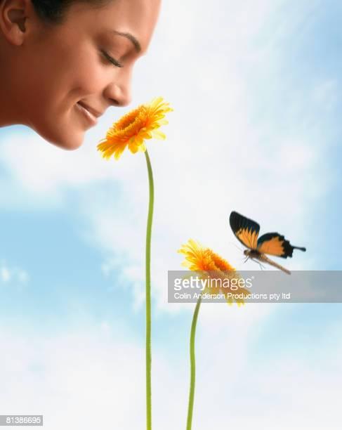 Hispanic woman smelling flower