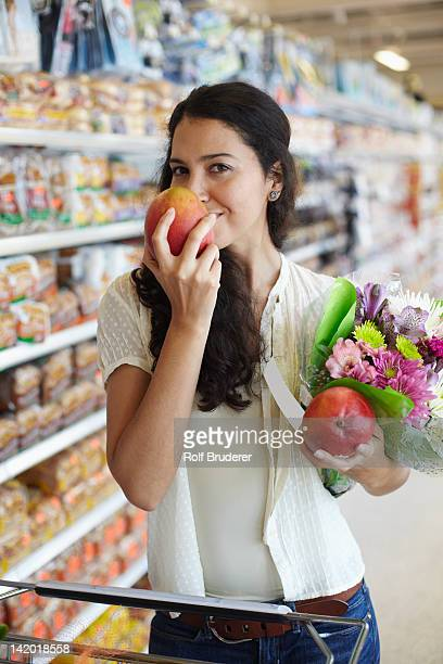 Hispanic woman smelling fruit in grocery store