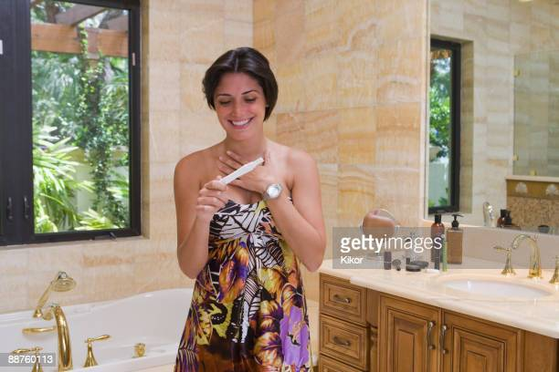 Hispanic woman smiling and holding pregnancy test in bathroom