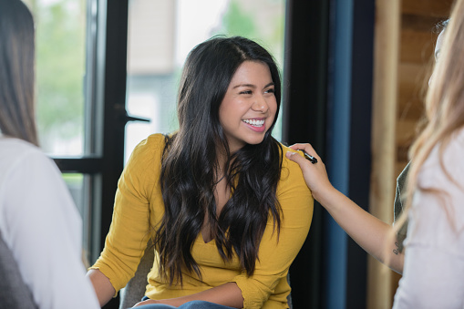Hispanic woman smiling during support group therapy meeting 1049086992