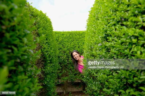 Hispanic woman smiling in hedge maze