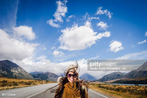 Hispanic woman smiling in road near mountains