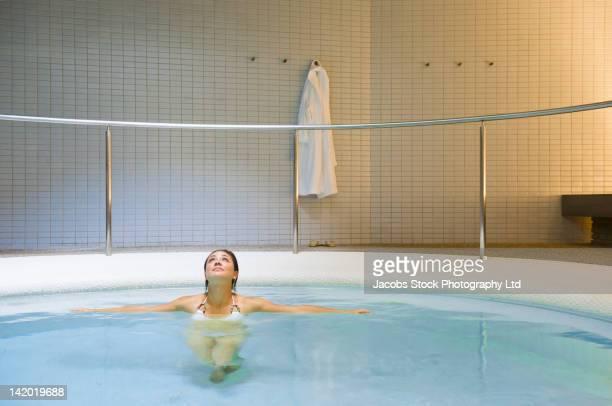 Hispanic woman soaking in hot tub