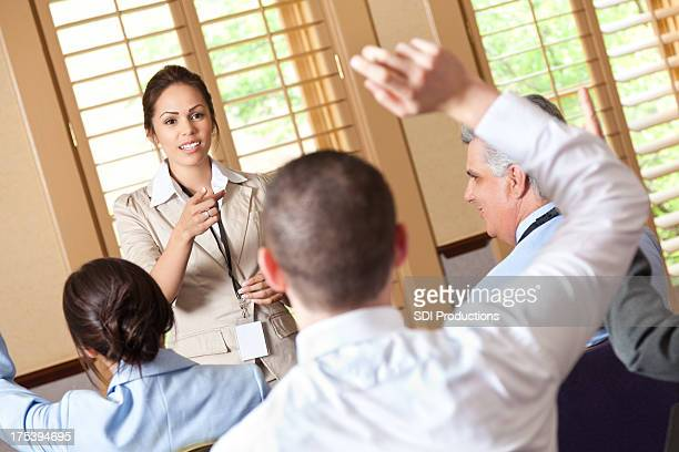 Hispanic woman speaking to a group of professionals