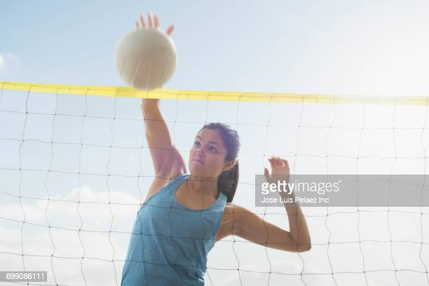 Hispanic woman spiking volleyball