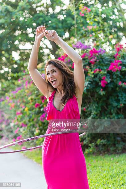 Hispanic woman spinning plastic hoop outdoors
