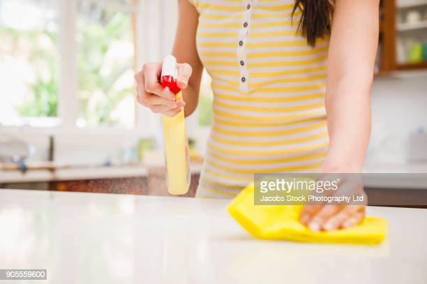 hispanic woman spraying and wiping counter - limpo - fotografias e filmes do acervo