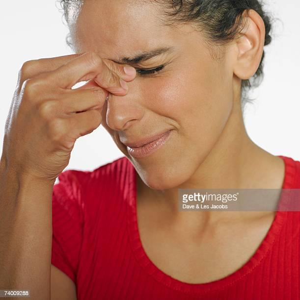 Hispanic woman squeezing bridge of nose
