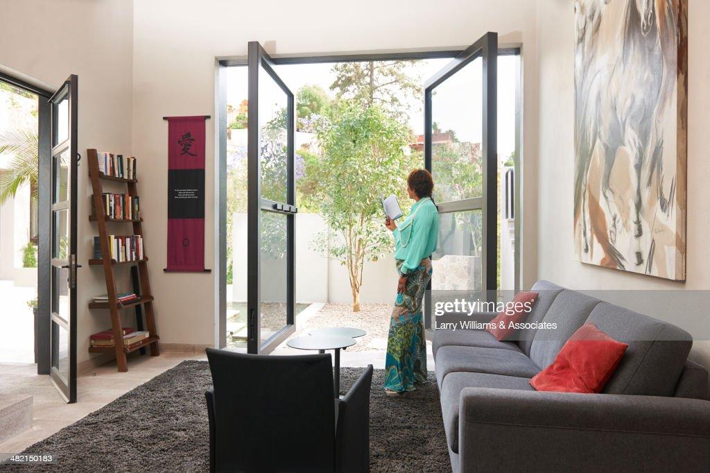 Hispanic woman standing at glass doors : Stock Photo