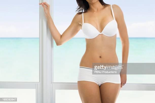 Hispanic woman standing at window