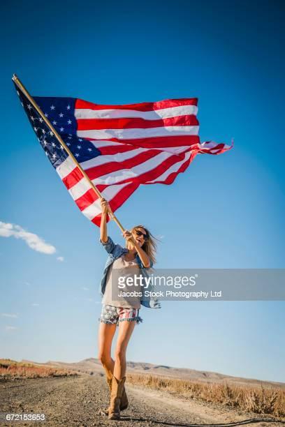Hispanic woman standing in desert waving American flag