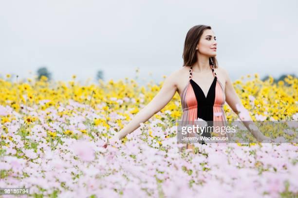 Hispanic woman standing in field of flowers