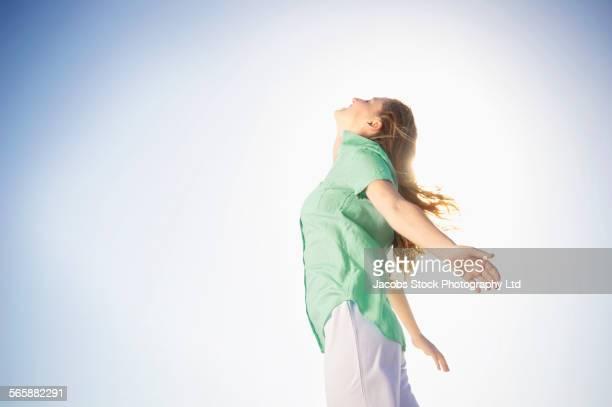 Hispanic woman standing in wind under blue sky