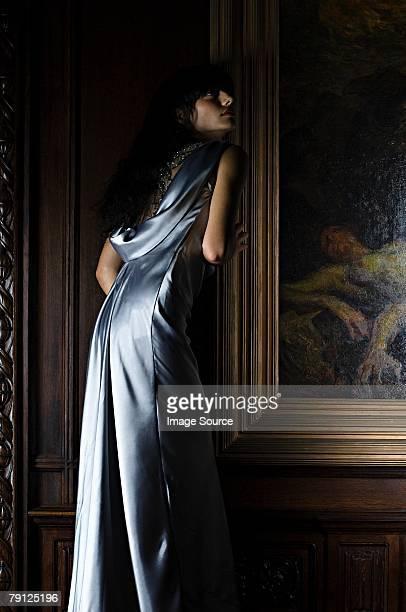 Hispanic woman standing near a painting