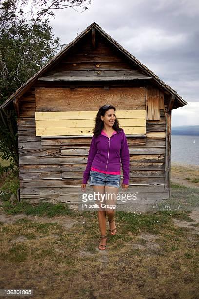 Hispanic woman standing near wooden shed