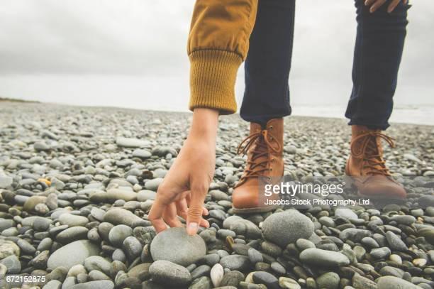Hispanic woman standing on beach reaching for rock