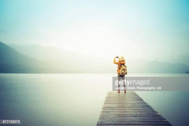 Hispanic woman standing on dock at lake photographing mountain