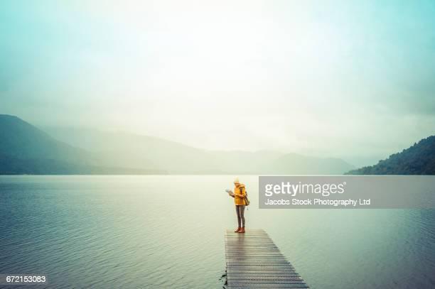 Hispanic woman standing on dock at mountain lake reading map
