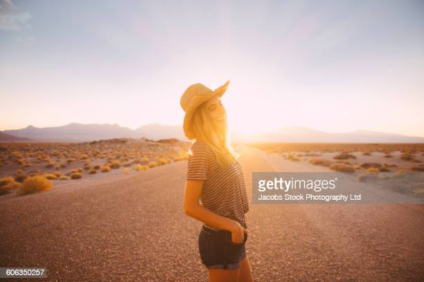 Hispanic woman standing on remote road