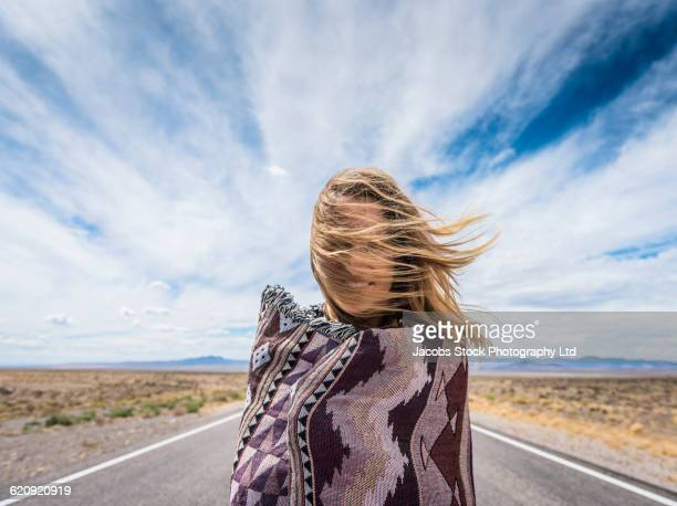 hispanic woman standing on remote road - nevada stock pictures, royalty-free photos & images