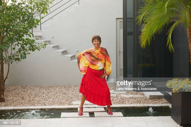 Hispanic woman standing on steps over pond