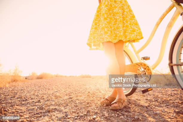 Hispanic woman standing with bicycle on dirt road