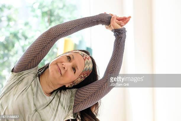 Hispanic woman stretching arms