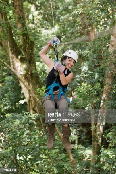 Hispanic woman swinging on zip line,