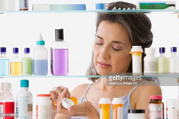Hispanic woman taking medication in bathroom