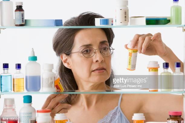 hispanic woman taking medication in bathroom - armoire de toilette photos et images de collection
