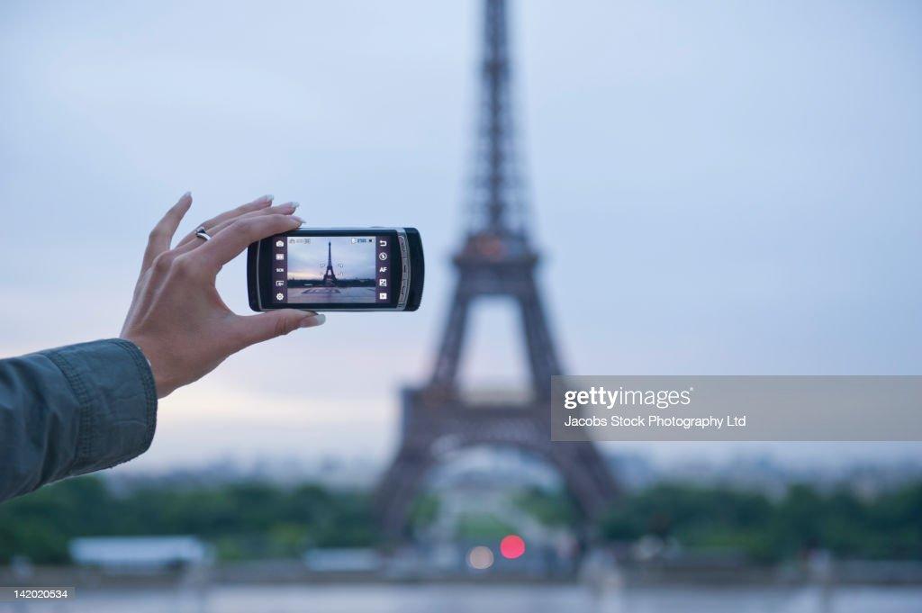 Hispanic woman taking photograph of Eiffel Tower : Stock Photo