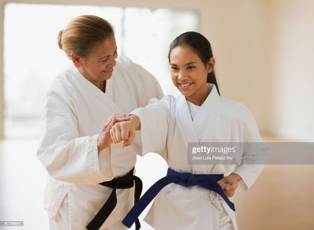 Hispanic woman teaching girl martial arts : Stock Photo