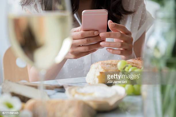 Hispanic woman texting on cell phone at table