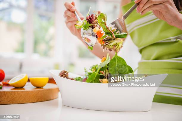 hispanic woman tossing salad in domestic kitchen - salad stock pictures, royalty-free photos & images